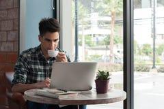 Homme d'affaires utilisant l'ordinateur portable avec le comprimé et stylo sur la table en bois dedans Images libres de droits