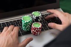 Homme d'affaires utilisant l'ordinateur portable avec les jetons de poker empilés Images libres de droits