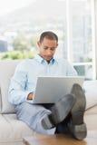 Homme d'affaires utilisant l'ordinateur portable avec ses pieds  Images stock