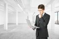 Homme d'affaires utilisant l'ordinateur portable dans l'intérieur vide Photo stock
