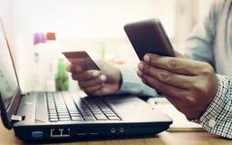 Homme d'affaires utilisant l'ordinateur portable et le téléphone portable aux achats en ligne photographie stock libre de droits