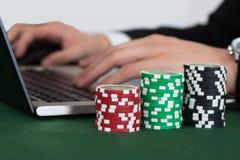 Homme d'affaires utilisant l'ordinateur portable par les puces empilées de casino Photographie stock libre de droits