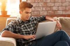 Homme d'affaires utilisant l'ordinateur portable sur le sofa dans le café image stock