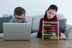 Homme d'affaires utilisant l'ordinateur portable tandis que collègue féminin comptant avec l'abaque photo stock