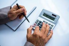 Homme d'affaires utilisant la calculatrice et les notes de prise Image stock