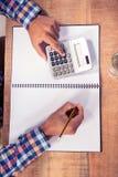 Homme d'affaires utilisant la calculatrice tout en écrivant sur le livre Images libres de droits