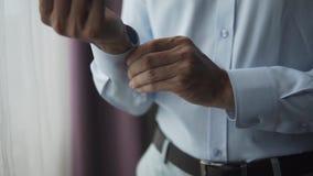 Homme d'affaires utilisant la chemise et le bouton bleus de couleur vers le haut des douilles et allant travailler dans le costum banque de vidéos