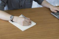 homme d'affaires utilisant la note de calculatrice et d'écriture sur le bloc-notes Images stock