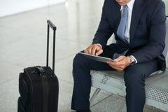 Homme d'affaires utilisant la tablette dans l'aéroport Image stock