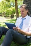 Homme d'affaires utilisant la tablette en parc Image stock