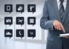 Homme d'affaires utilisant le comprimé à côté des icônes digitalement produites d'APP photographie stock libre de droits