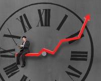 Homme d'affaires utilisant le comprimé et se reposer sur la flèche rouge de croissance avec du Cl Images stock