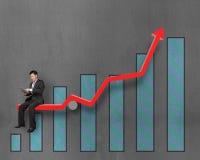Homme d'affaires utilisant le comprimé et se reposer sur la flèche rouge de croissance avec le ch Photo libre de droits