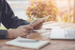 Homme d'affaires utilisant le comprimé fonctionnant avec l'ordinateur portable et le téléphone portable image stock