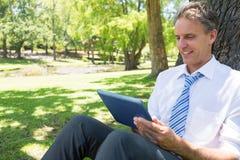 Homme d'affaires utilisant le comprimé numérique en parc Photo stock