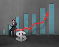 Homme d'affaires utilisant le comprimé se reposant sur la flèche rouge de croissance avec l'argent Image stock