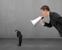 Homme d'affaires utilisant le mégaphone hurlant à son employé avec le concret Images stock