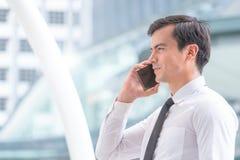 Homme d'homme d'affaires utilisant le téléphone dans la ville moderne photographie stock libre de droits