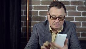 Homme d'affaires utilisant le téléphone dans une chambre avec un mur de briques clips vidéos