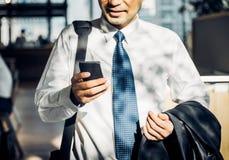 Homme d'affaires utilisant le téléphone portable à la causerie avec l'ami après wor Images libres de droits