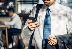 Homme d'affaires utilisant le téléphone portable à la causerie avec l'ami après wor Photos stock