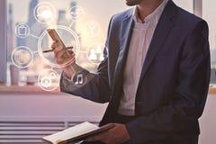 Homme d'affaires utilisant le téléphone portable avec le diagramme d'affaires Image stock