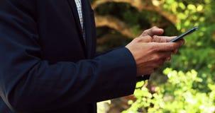 Homme d'affaires utilisant le téléphone portable en parc 4k banque de vidéos