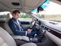 Homme d'affaires utilisant le téléphone portable et le service de mini-messages tout en conduisant ne pas prêter l'attention à la photo stock