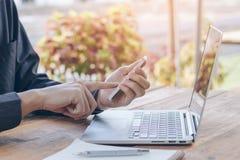 Homme d'affaires utilisant le téléphone portable fonctionnant avec l'ordinateur portable sur la table en bois photos stock