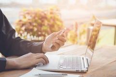 Homme d'affaires utilisant le téléphone portable fonctionnant avec l'ordinateur portable sur la table en bois photo stock