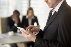 Homme d'affaires utilisant le téléphone portable lors de la réunion dans le bureau Photographie stock libre de droits