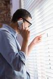 Homme d'affaires utilisant le téléphone portable tout en regardant par des abat-jour dans le bureau Images stock
