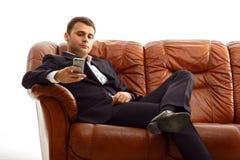 Homme d'affaires utilisant le téléphone se reposant sur le divan Photos stock