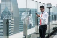 Homme d'affaires utilisant le téléphone sur le dessus d'un bâtiment moderne Photos libres de droits