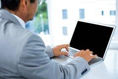 Homme d'affaires utilisant son ordinateur portatif Photo stock