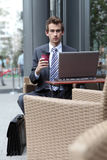 Homme d'affaires utilisant son ordinateur portatif en café Photo stock