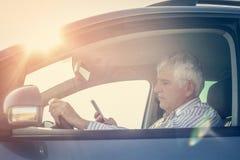 Homme d'affaires utilisant un téléphone, se reposant dans la voiture Photographie stock libre de droits