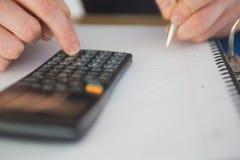 Homme d'affaires utilisant une calculatrice et une écriture Photo stock