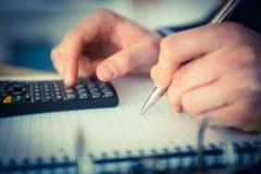 Homme d'affaires utilisant une calculatrice et une écriture Photos libres de droits