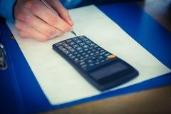 Homme d'affaires utilisant une calculatrice et une écriture Images libres de droits