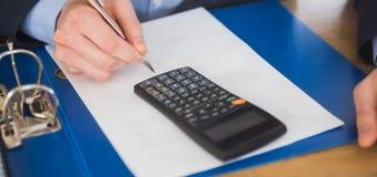 Homme d'affaires utilisant une calculatrice et une écriture Image stock