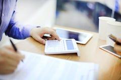 Homme d'affaires utilisant une calculatrice pour calculer des nombres image libre de droits
