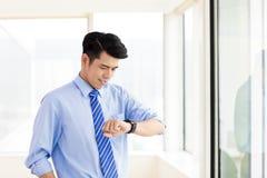 Homme d'affaires vérifiant le temps de la montre dans le bureau photo stock