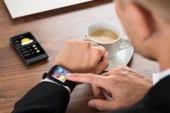 Homme d'affaires vérifiant le temps sur le smartwatch image stock