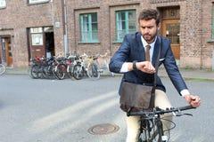 Homme d'affaires vérifiant le temps tout en permutant sur sa bicyclette image stock