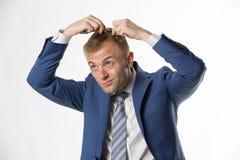Homme d'affaires vérifiant ses cheveux indiquant la perte des cheveux images libres de droits