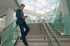 Homme d'affaires vérifiant son comprimé Photographie stock libre de droits
