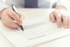 Homme d'affaires vérifiant un rapport de gestion Image stock