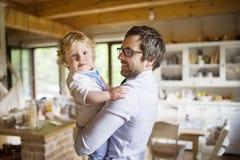 Homme d'affaires venant à la maison, jugeant son fils haut dans les bras Photos libres de droits