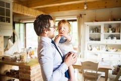 Homme d'affaires venant à la maison, jugeant son fils haut dans les bras Image stock